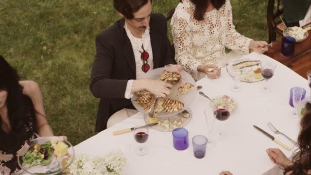 friends and family eating at an outdoor dinner party - bordsduk bildbanksvideor och videomaterial från bakom kulisserna