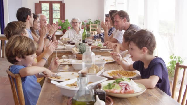 friends and family enjoying lunch at dining table - dining table stock videos & royalty-free footage