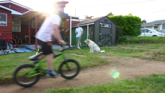 MS Friends and family hanging out in backyard while riding BMX bikes in backyard on summer afternoon