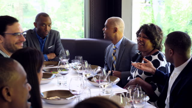 MS Friends and family in discussion during celebration meal in restaurant