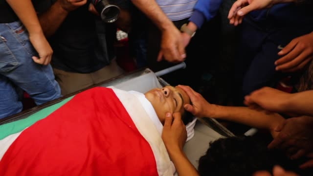 friends and family mourn over the body of jamal affana after he succumbed to a gunshot wound sustained during protests last friday at the gaza border... - 2018年ガザ地区国境抗議点の映像素材/bロール