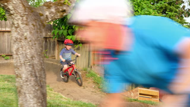 pan friends and family riding bmx bikes on backyard dirt track on summer afternoon - bmx stock-videos und b-roll-filmmaterial