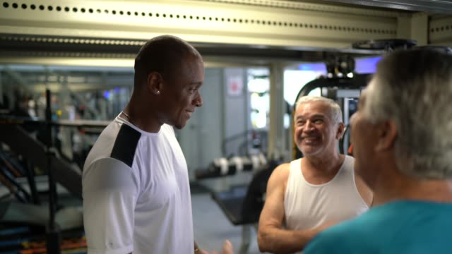friends and personal trainer talking at the gym - aerobics stock videos & royalty-free footage