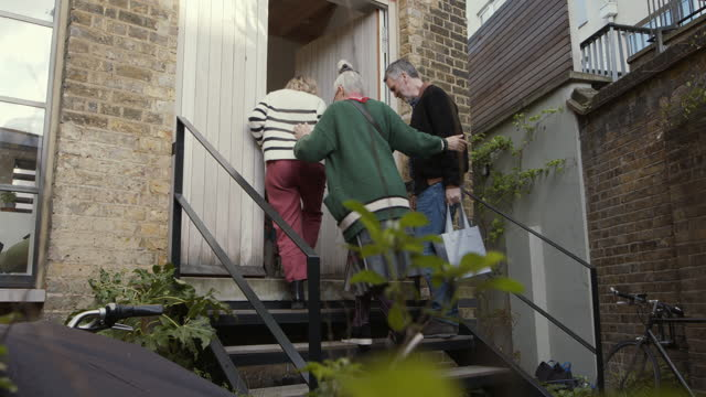friends arriving at house and entering through front door - multi generation family stock videos & royalty-free footage