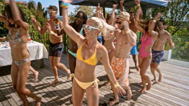 friends at a pool party dancing a group dance in their bathing suits on a hot day - coda di cavallo video stock e b–roll