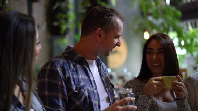 freunden in einem restaurant genießen sie getränke, reden und lachen - erwachsene person stock-videos und b-roll-filmmaterial