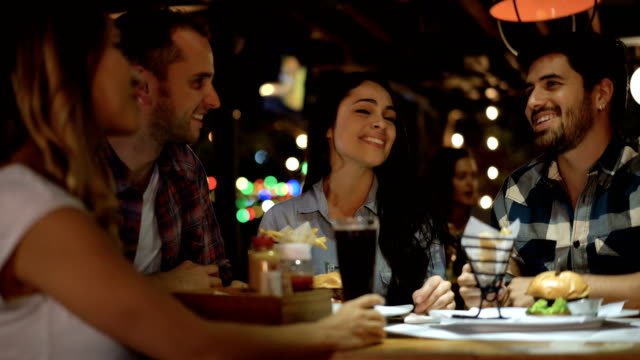 Friends at a restaurant enjoying junk food and talking looking very happy
