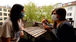 Friends at home talking wearing a mask