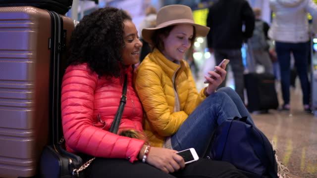 vídeos y material grabado en eventos de stock de amigos en el vestíbulo del aeropuerto esperando el vuelo - de ascendencia mixta