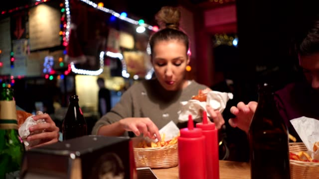 friends at the pub eating burgers and fries - hamburger stock videos & royalty-free footage