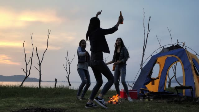 friends camping drinking,they are dancing around a camp fire.camping,summer holidays and vacation concept.camping - camp fire stock videos & royalty-free footage