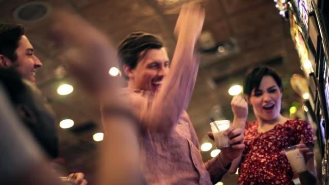 stockvideo's en b-roll-footage met friends celebrate as guy hits jackpot on slot machine in vegas casino - houten paal
