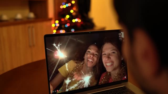 friends celebrating christmas on video call during covid-19 pandemic - conference call stock videos & royalty-free footage