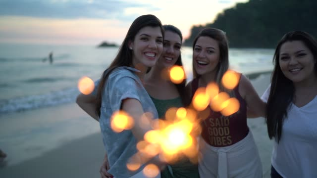 friends celebrating new year with sparkler at beach - wishing well stock videos & royalty-free footage