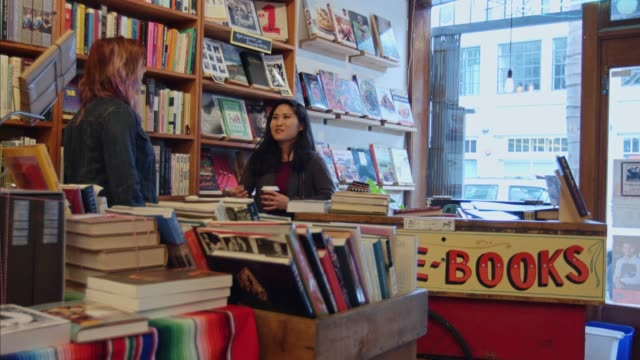 friends chatting in bookstore - bookstore stock videos & royalty-free footage