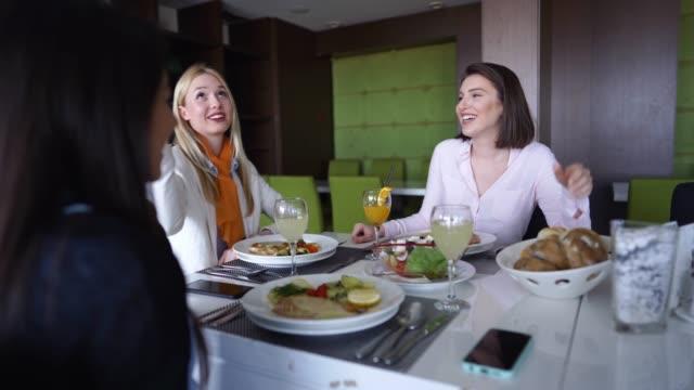 レストランでランチのおしゃべりをする友達 - デリカッセン点の映像素材/bロール