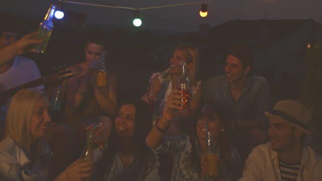 Amigos animando en fiesta en la azotea por la noche