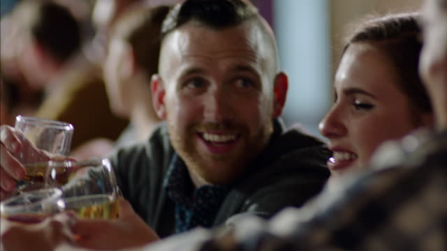 friends cheers and clink glasses in crowded bar - lokal stock-videos und b-roll-filmmaterial