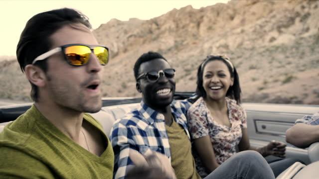 vídeos y material grabado en eventos de stock de friends clasp hands in the back of classic convertible on desert road trip - vehículo terrestre