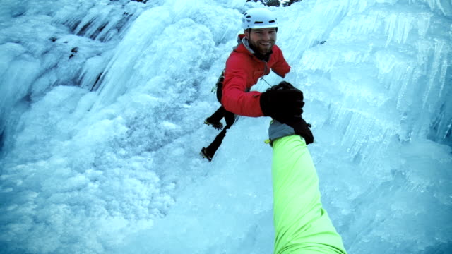 pov friends climbing the ice and shaking hands - climbing stock videos & royalty-free footage