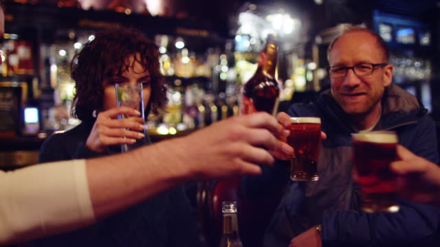 friends clinking glasses in pub - pub stock videos & royalty-free footage