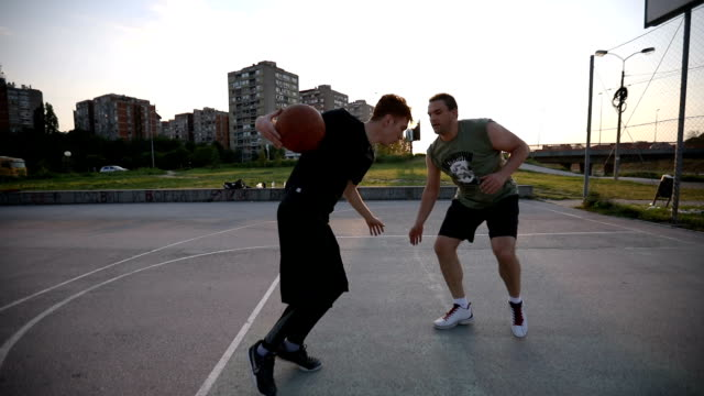 friends competing in a game of basketball - dribbling stock videos & royalty-free footage