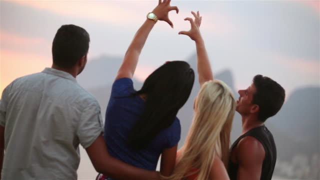 Friends connect hands to make heart shape at sunset on the beach at Ipanema
