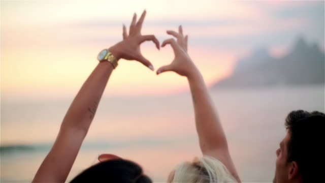 friends connect hands to make heart shape at sunset on the beach at ipanema - three people stock videos & royalty-free footage