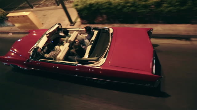 vidéos et rushes de friends cruise through urban streets at night in classic convertible - aller tranquillement