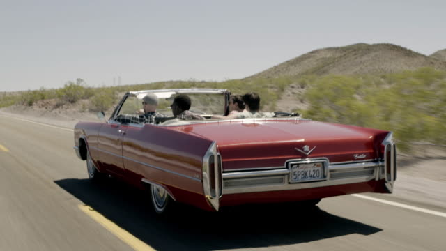 Friends cruise up lonely desert road in classic convertible