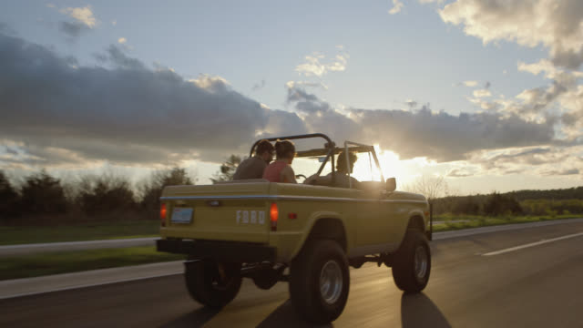 Friends cruising in classic Ford Bronco speed up into the sunset