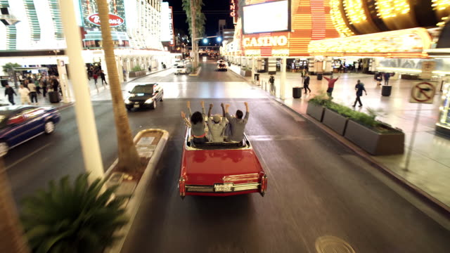 Friends cruising through downtown Las Vegas in classic convertible climb up on backseat and cheer