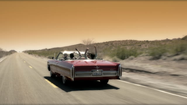 Friends cruising up lonely desert road throw hands in the air and cheer