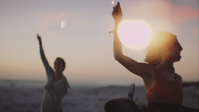 freunde mit wunderkerzen dacing um am strand - party stock-videos und b-roll-filmmaterial