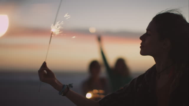 Friends dacing around with sparklers at the beach