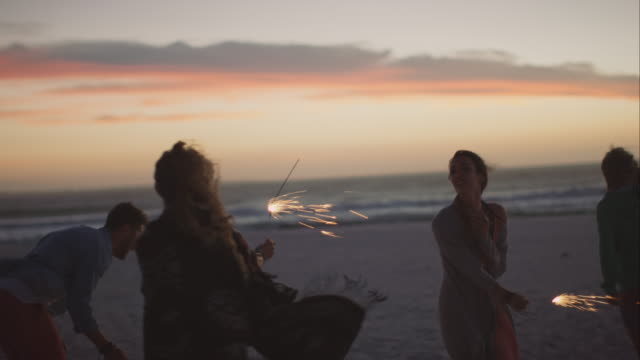friends dacing around with sparklers at the beach - sparkler stock videos & royalty-free footage