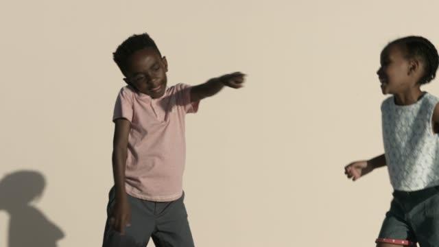 vídeos de stock e filmes b-roll de friends dancing against beige background - fotografia de três quartos