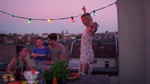 vidéos et rushes de friends dancing on urban rooftop - haut