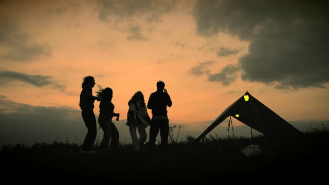 friends dancing outside their tent at sunset silhouetted by the sky - tent stock videos & royalty-free footage