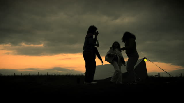 friends dancing to music outside of their tent at sunset silhouetted by the sky - east sussex stock videos & royalty-free footage