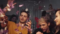 Friends dancing with confetti at home in Christmas