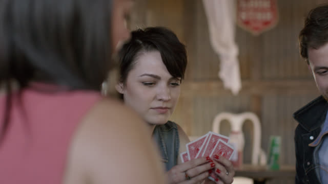 friends deal poker cards and look at their hands in competitive game - カードゲーム点の映像素材/bロール