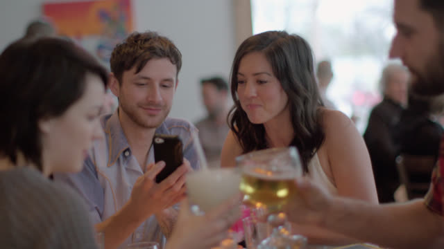 friends dining in restaurant look at funny photos on smartphone - arbeitskollege stock-videos und b-roll-filmmaterial