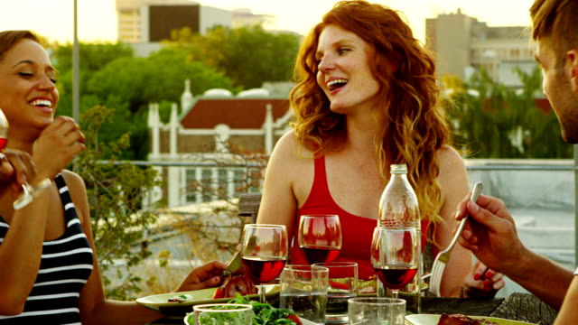 Friends dining on rooftop deck of building