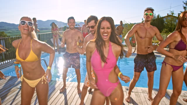 Friends doing a group dance by the pool in their bathing suits on a hot summer day