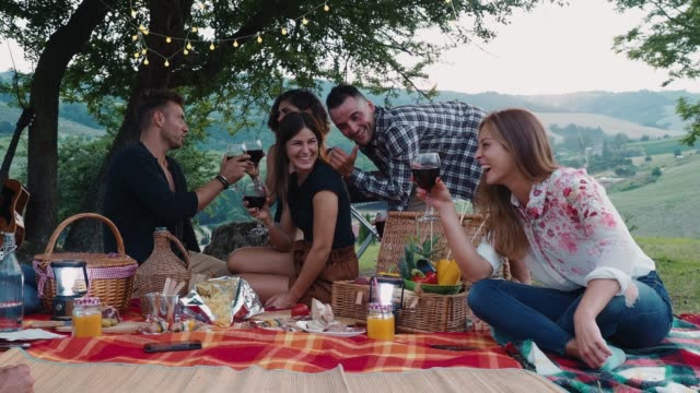 Friends doing a picnic together at sunset in the countryside