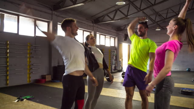 ws friends doing high fives after workout in gym - motivation stock-videos und b-roll-filmmaterial