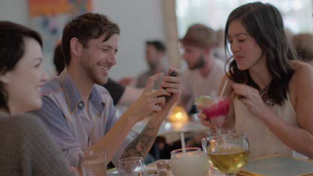 Friends drink in Austin restaurant and laugh at photo on smartphone