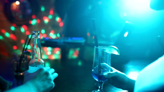 friends drinking alcohol at bar in night club with female dj in background - club dj stock videos & royalty-free footage