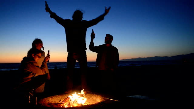 Friends Drinking Beer at Beach Bonfire